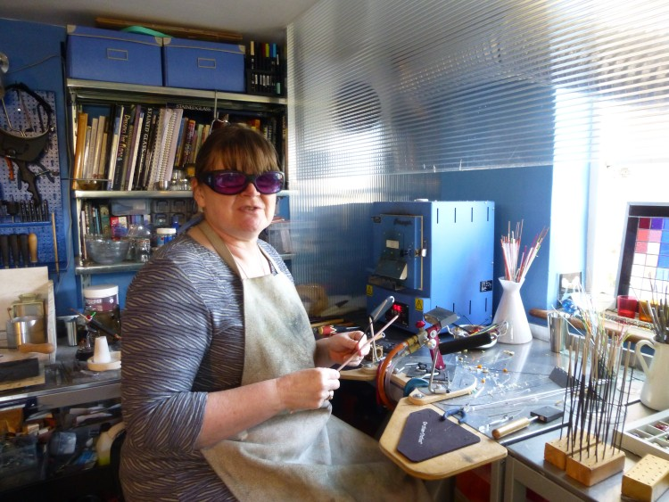 Cathy Allen in her studio, wearing protective glasses and apron