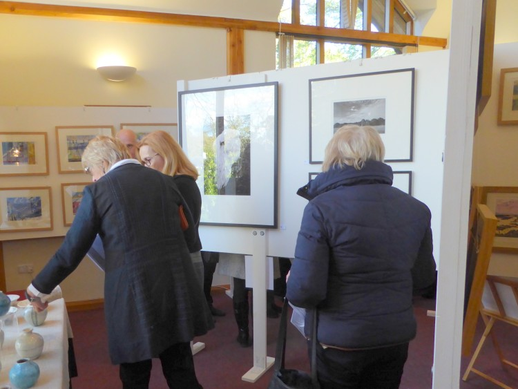 A group viewing Rob Wheeler's ceramics, with Richard Hayward's photographs visible to the right.
